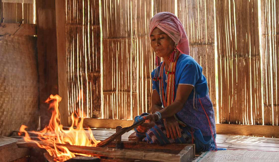 Woman in a bamboo hut cooking on fire