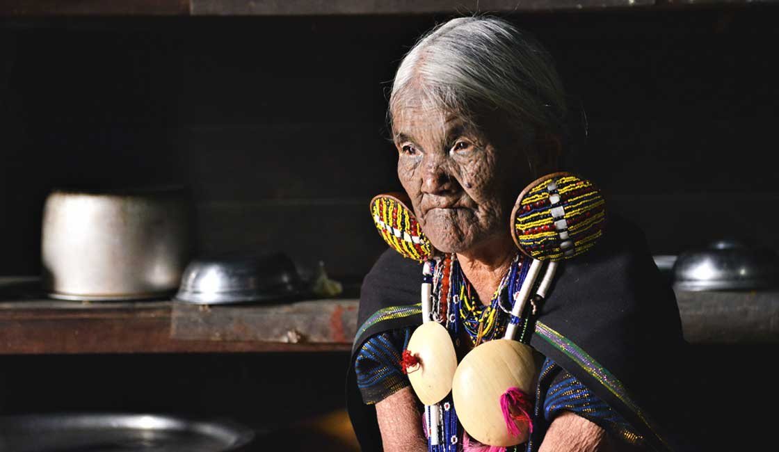 Elderly lady with tattoos on her face in Chin State