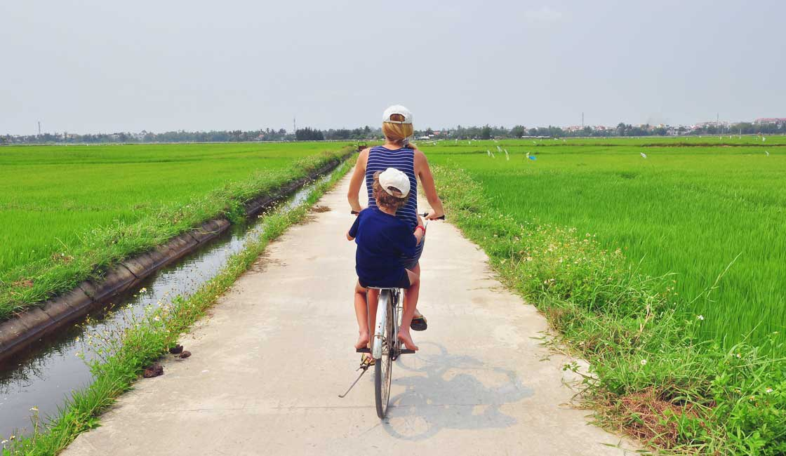 Mother and a kid on a bicycle in a Vietnamese countryside