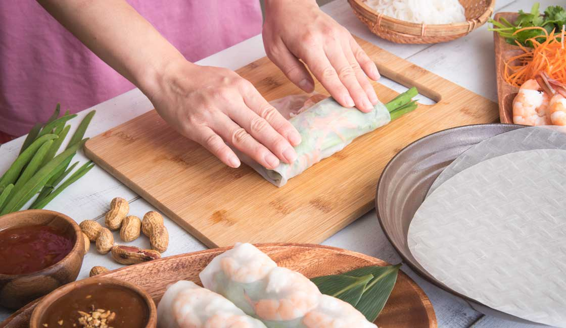 Closeup on hands making a fresh spring roll