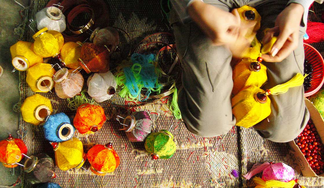 Person making small colourful lanterns