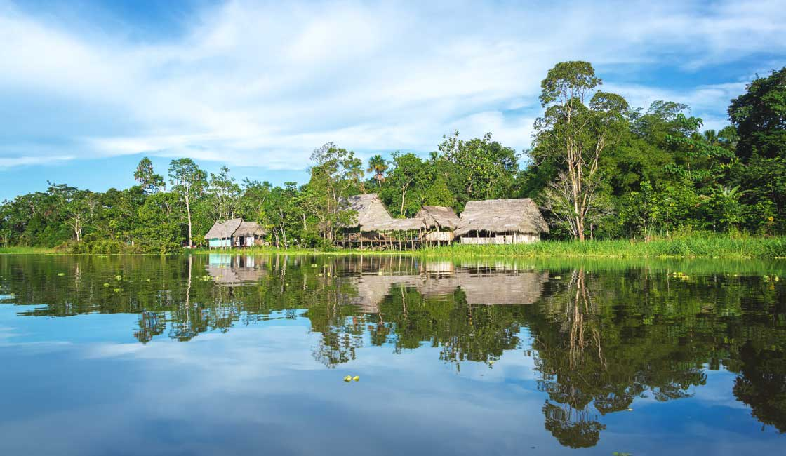 Stilted houses reflecting in the river