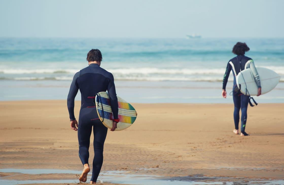 surfers walking towards the sea