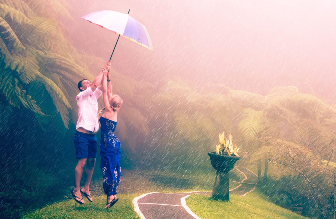 couple jumping in the rain holding an umbrella