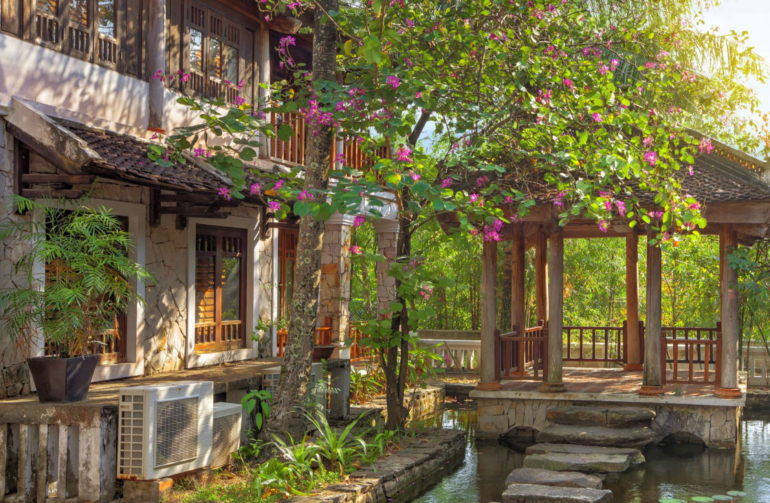 hotel surround by trees and flowers