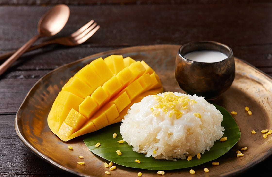 Mango Sticky Rice over a wooden table and copper fork and spoon