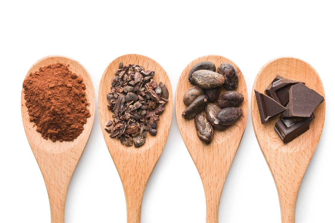Cacao And Dark Chocolate On Wooden Spoons on White Background