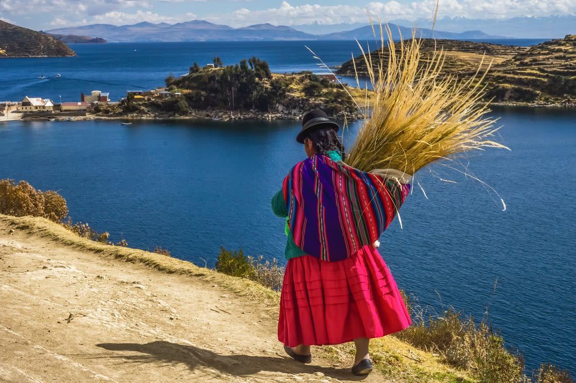 Bolivian Woman In Traditional Dress Walking Trought The Sun Island, Lake Titicaca