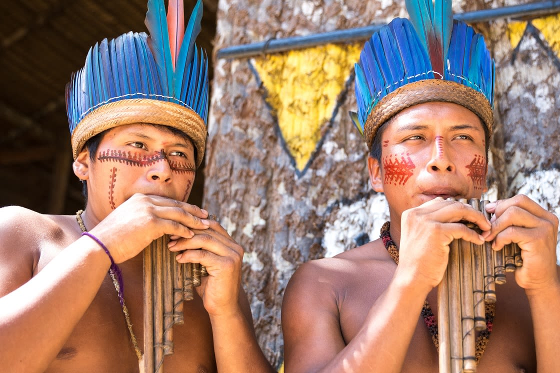 Native Brazilian Guys Playing Wooden Flute At An Indigenous Tribe