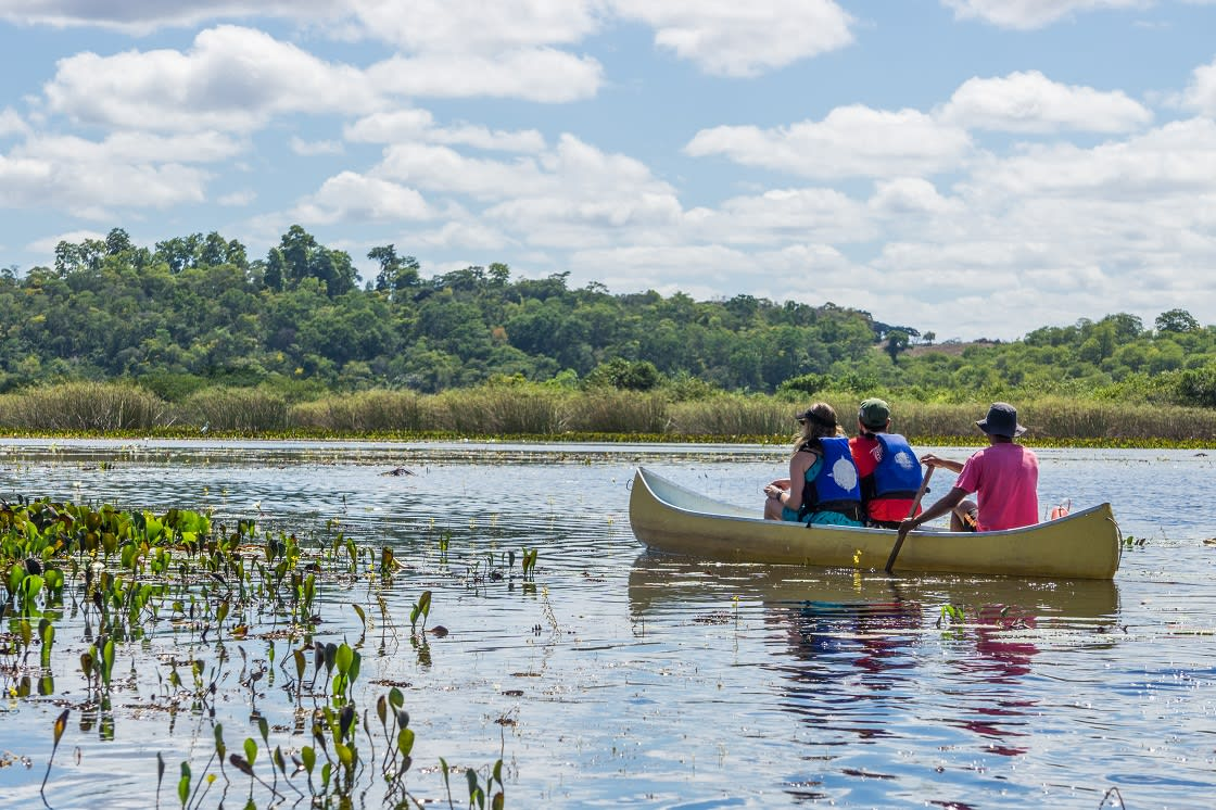 Tourists And Guide In A Canoe At Pantanal