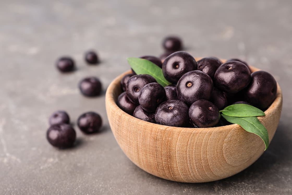 Bowl Of Fresh Acai Berries On Grey Stone Table