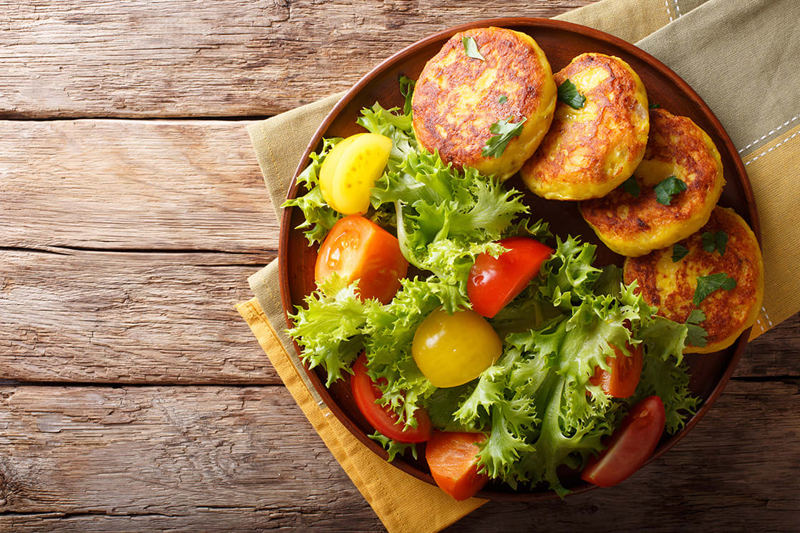 Freshly Prepared Potato Pancakes Are Served With Fresh Salad Close-up