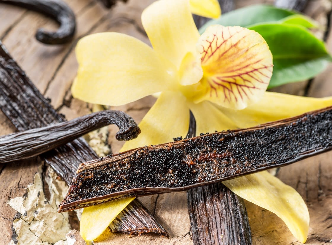 Dried Vanilla Stick And Orchid On Wooden Table