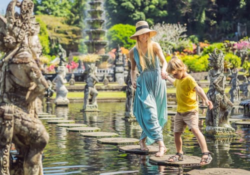 mommy and son walking throught a water garden full of stone statues