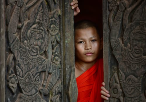 Monk novice looking out from the wooden carved door
