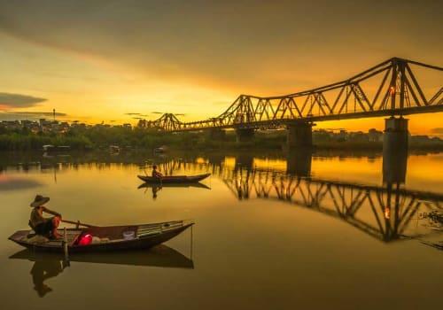 Small fishing boat at sunset near the bridge