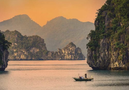 Small boat in Halong Bay at sunset