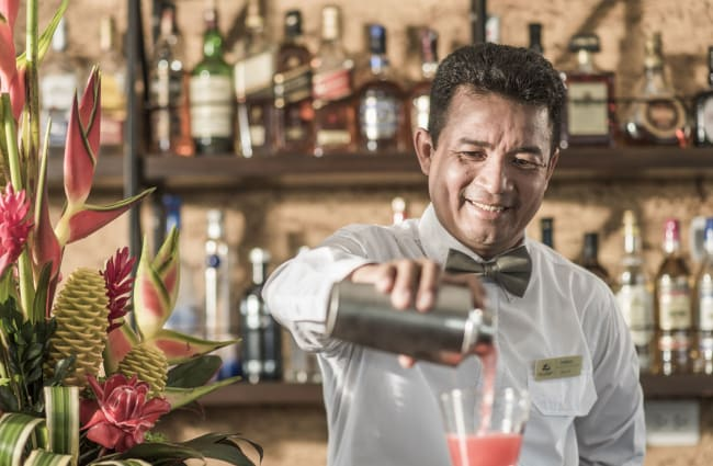 Smiling bartender pouring a drink