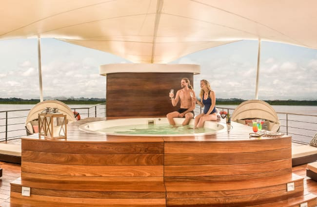 A couple in a jacuzzi on the cud deck