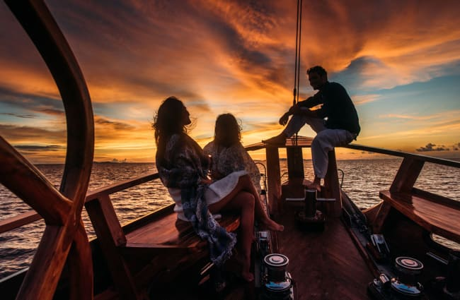 People sitting at the bow at sunset