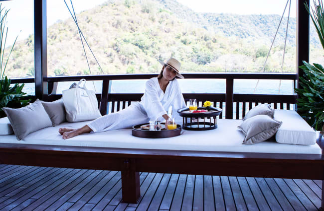 Woman relaxing and having breakfast on a daybed