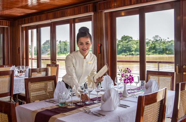 A stewardess preparing the table onboard Angkor Pandaw