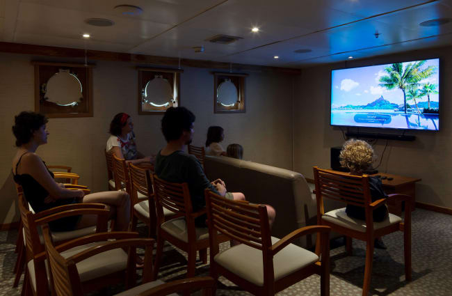 Passengers watching a movie in the auditorium room