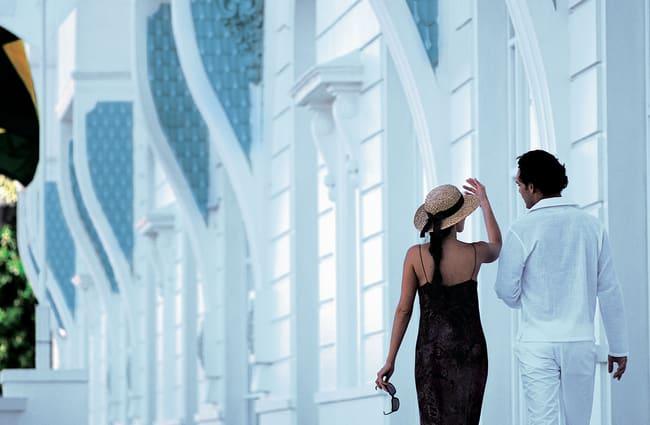 couple walking in front of belmond Rio