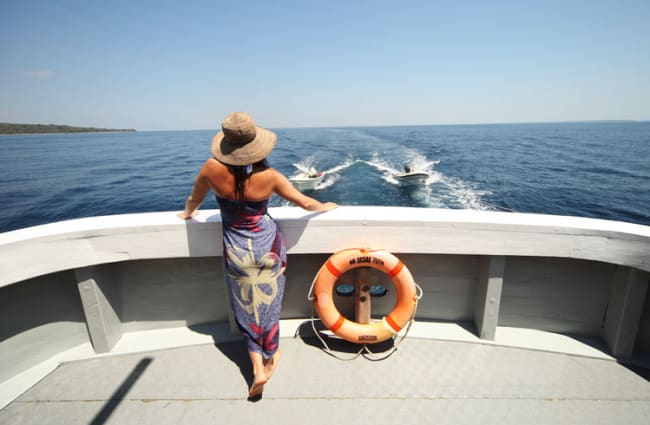 A woman standing on a rear of the boat
