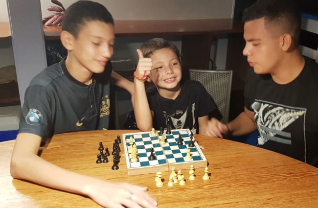 Family playing chess by the table