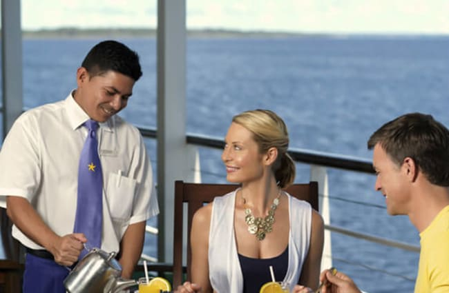 A coulple and a waiter on a sun deck