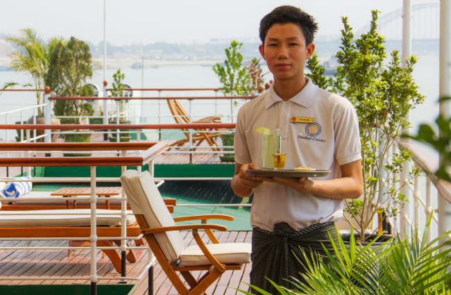 Waiter with a drink on the deck