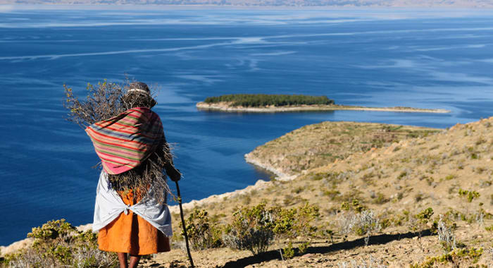 Old woman walking shore lake titicaca
