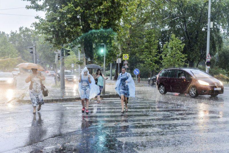 Gyalogosok futnak át az úttesten az esőben Budapesten, az Állatkerti sétányon – Fotó: Kallos Bea / MTI | ClimeNews