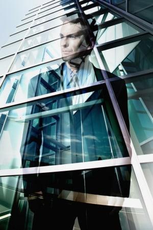 Kép:Fotolia (Reflection of businessman in office windows) | A zöldülés a nyereséget növeli - ClimeNews
