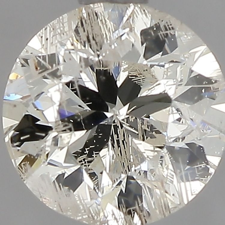 Round diamond that has jagged white lines throughout due to laser drilling