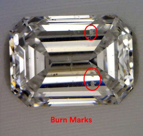 Rectangular step cut diamond with rough cloudy spots circled in red
