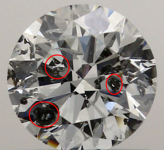A round diamond against a gray background with very large black crystals circled in three places