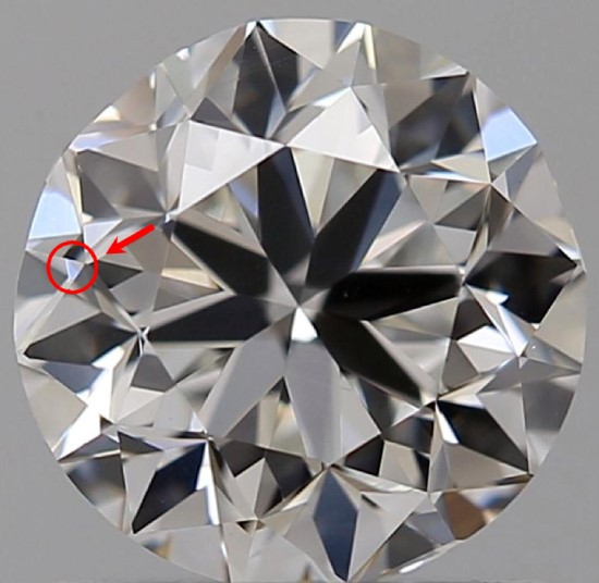A round diamond against a gray background has a red circle and arrow pointing to an extra facet on the table
