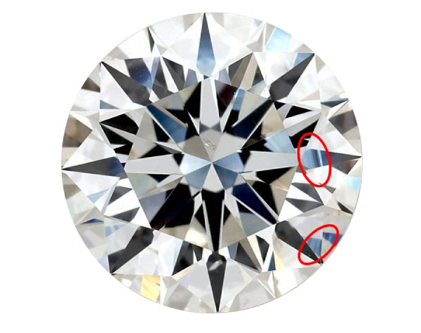 """Round diamond against a white background with two circles around lines on the diamond called """"surface graining"""""""