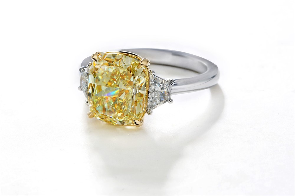 Yellow cushion cut diamond with white trapezoid side stones