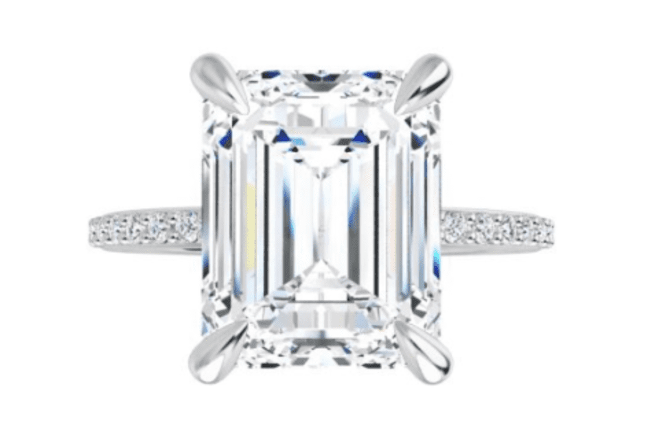 Emerald cut diamond in a prong setting with a pave band