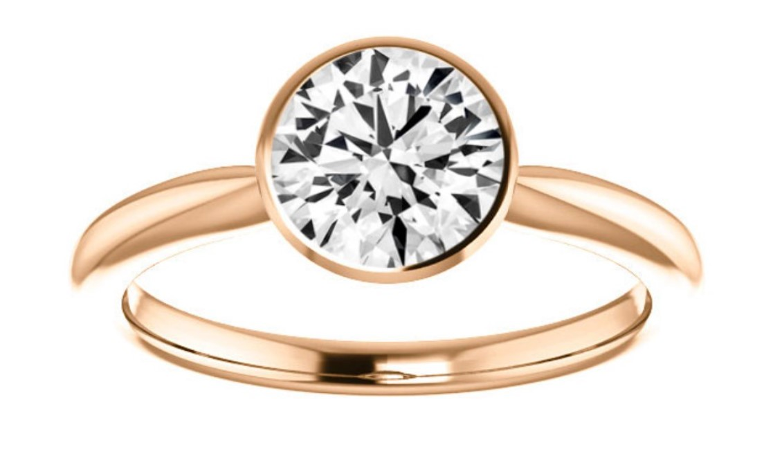 A round diamond in a rose gold bezel set solitaire ring
