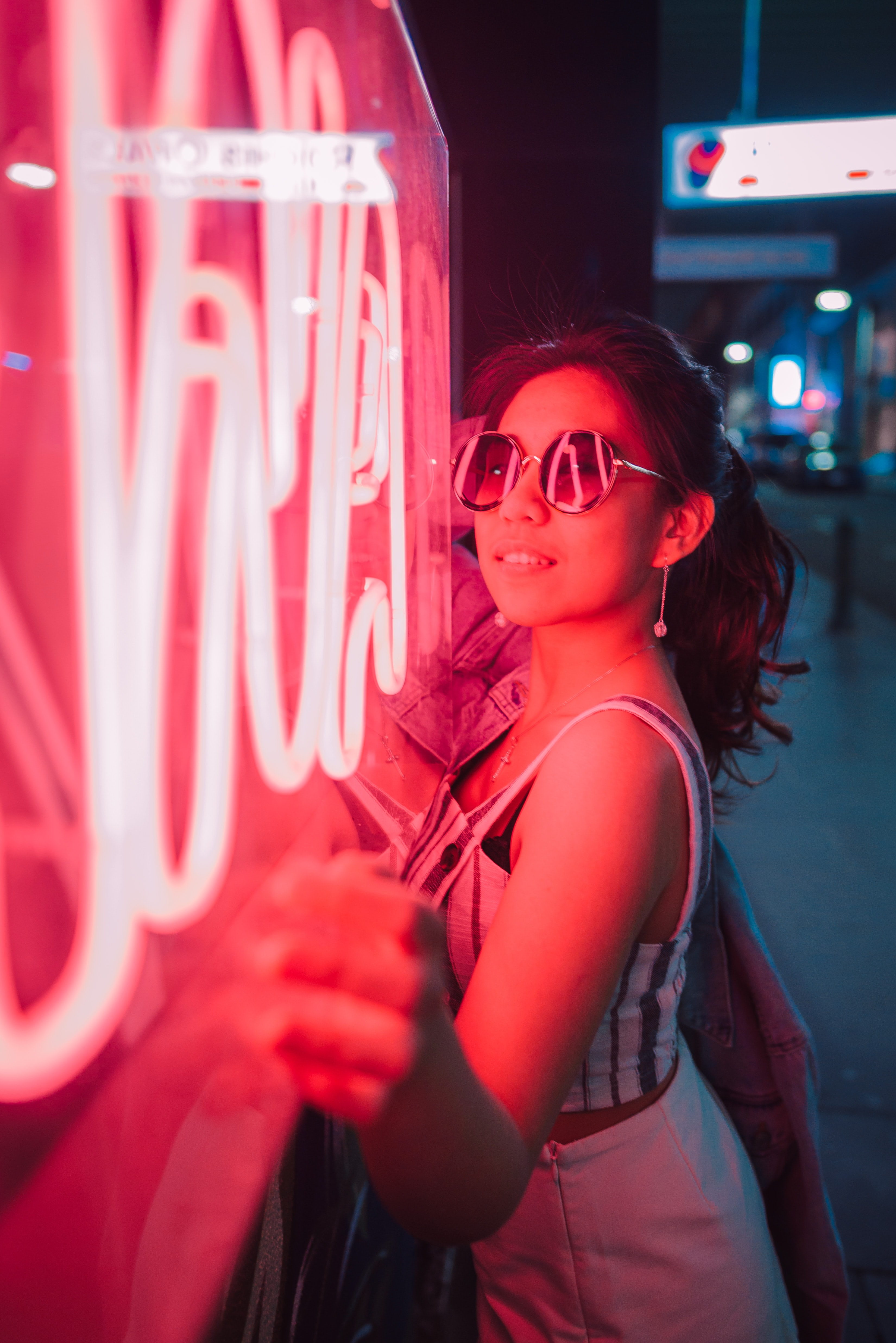young girl in fron of rose neon store