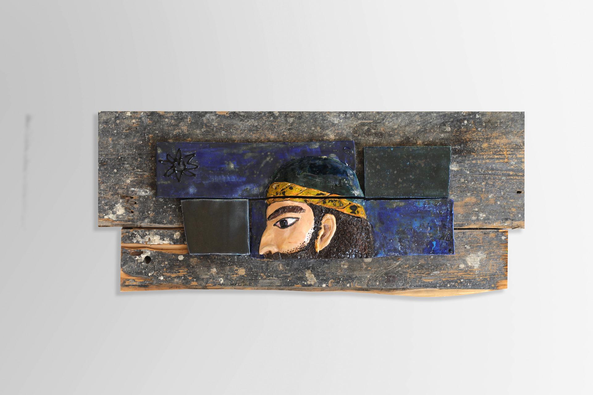 A piece of relief. Warrior head on the Victorian wooden floorboard. Souvenir.