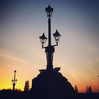 A traditional gas style lamp post against a sunset