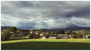 Stormy clouds hover over the houses of the village of Hawes