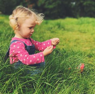 A little girl sat in the gradd wearing a bright pink flowery t-shirt and dungarees