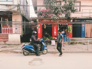 A man on a motorbike and a man walking in front of a nepalese shop front