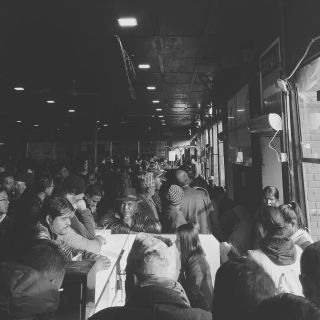 Groups of people waiting for a flight in an airport in black and white